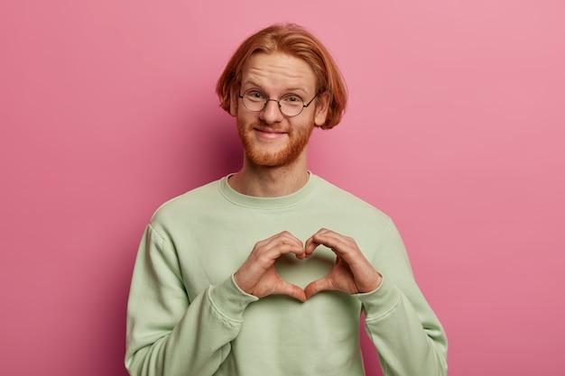 Homme barbu au gingembre montre le symbole du cœur de la main, avoue amoureux