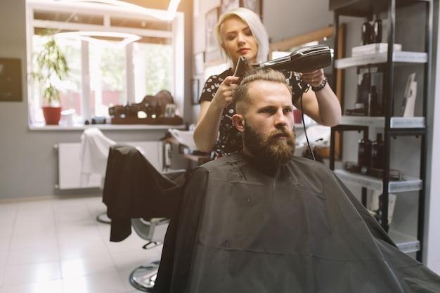 Homme barbu au salon de coiffure avec sèche-cheveux assis dans une chaise au salon de coiffure.