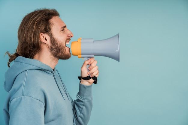 Homme barbu aux cheveux longs avec un haut-parleur dans ses mains.