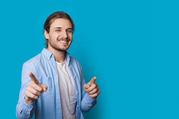 Homme barbu aux cheveux longs pointe la caméra sur un mur bleu avec de l'espace libre dans des vêtements décontractés