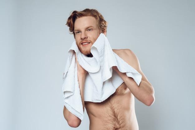 Homme barbu aux cheveux rouges essuie le visage avec une serviette.