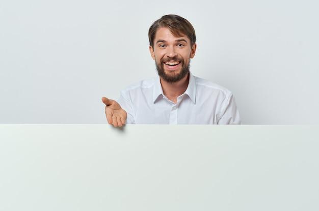 Homme barbu bannière blanche à la main présentation de la feuille vierge fond blanc. photo de haute qualité