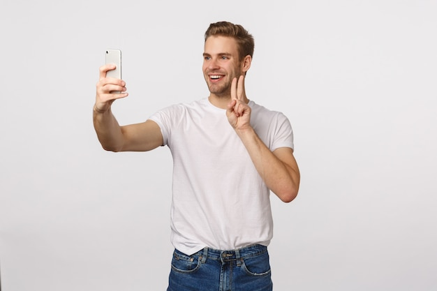 Homme barbu blond séduisant en t-shirt blanc prenant selfie