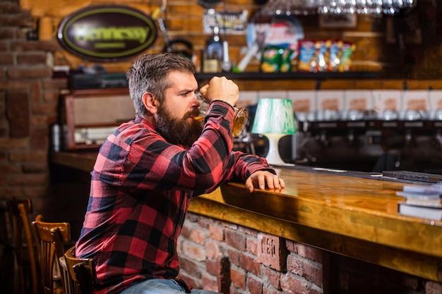 Un homme barbu boit de la bière dans un bar.