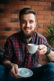 Un homme barbu boit du café au café. loisirs de sexe masculin dans un pub