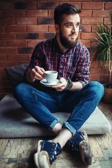 Un homme barbu boit du café au café