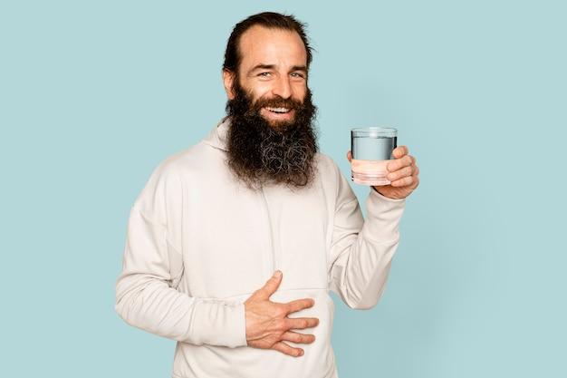 Homme barbu en bonne santé tenant un verre d'eau