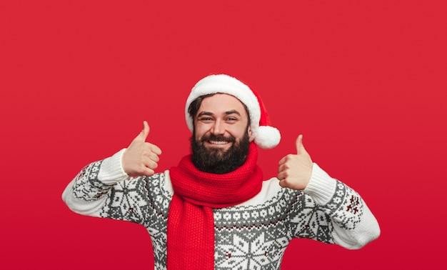 Homme barbu en bonnet de noel faisant des gestes pouces vers le haut