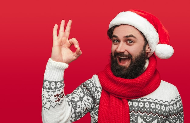 Homme barbu en bonnet de noel montrant le geste ok