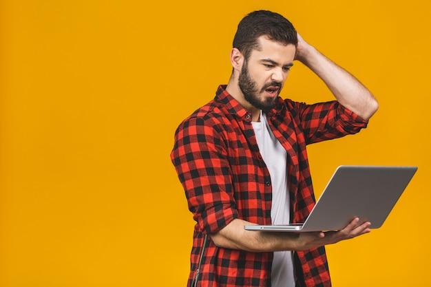 Homme barbu bouleversé en colère à lunettes tenant un ordinateur portable et hurlant isolé sur mur jaune.