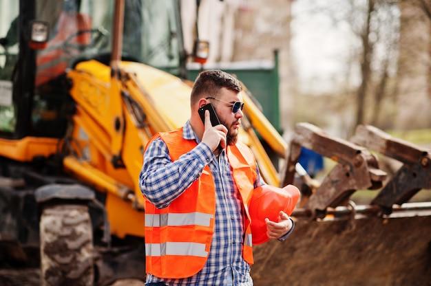 Homme barbu brutal costume costume ouvrier du bâtiment dans le casque de sécurité orange, lunettes de soleil contre traktor avec téléphone portable à la main.