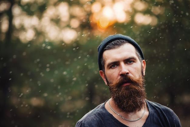 Homme barbu brutal avec une longue barbe et moustache dans un t-shirt et un chapeau chaud sur fond de forêt