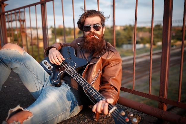 Homme barbu brutal avec une longue moustache dans des lunettes classiques noires se trouve en train de fumer une cigarette et joue de la guitare électrique sur l'asphalte