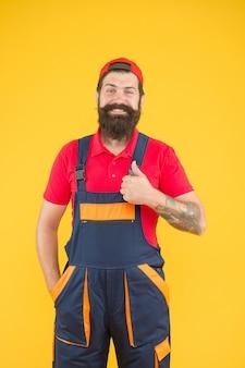Un homme barbu brutal en uniforme de service mécanique travaille comme plombier qualifié, livraison.