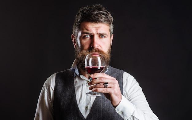 Homme barbu buvant du vin rouge. sommelier dégustation de vin au restaurant. verre de vin. de l'alcool.