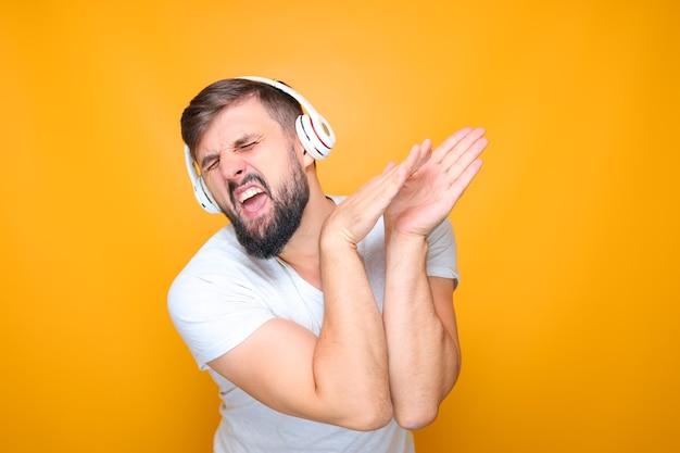 Un homme barbu avec un casque musical blanc écoute de la musique et chante en même temps.