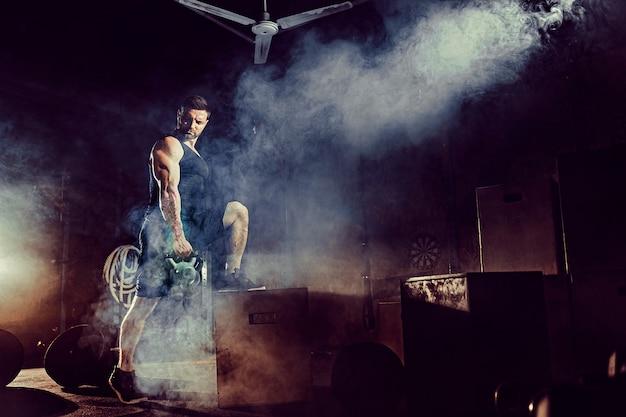 Homme barbu caucasien attrayant musculaire soulevant deux kettlebells dans une salle de sport. poids des plaques, haltères et pneus en arrière-plan.