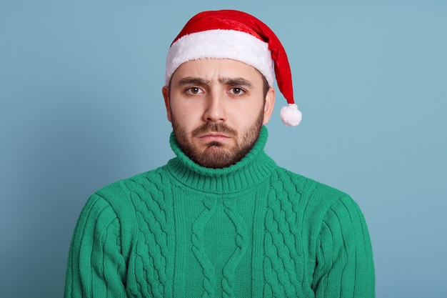 Homme barbu caucasien portant un élégant pull vert et un bonnet de noel isolé sur bleu, ayant une expression faciale bouleversée, a l'air triste, posant avec des lèvres boudeuses, étant de bonne humeur. concept de personnes.