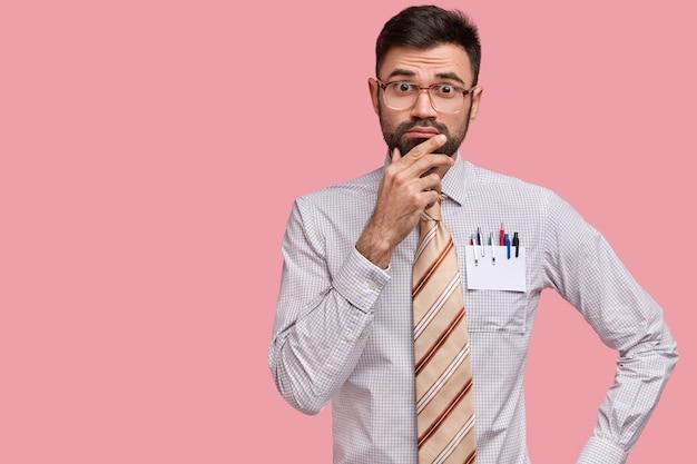 Homme barbu caucasien tient le menton, regarde avec doutes la caméra, habillé en chemise formelle, cravate