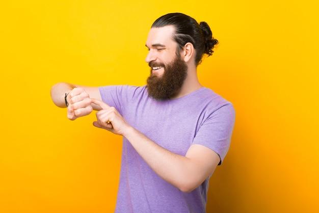 Homme barbu caucasien vérifie sa montre intelligente sur fond jaune.