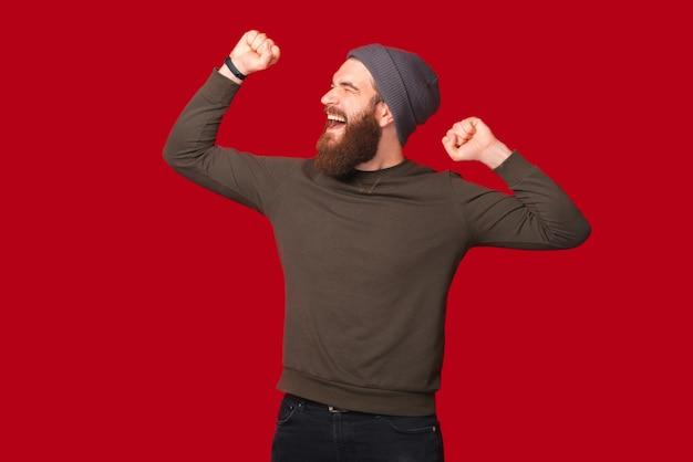 L'homme barbu célèbre la victoire en dansant et en faisant le geste du vainqueur.