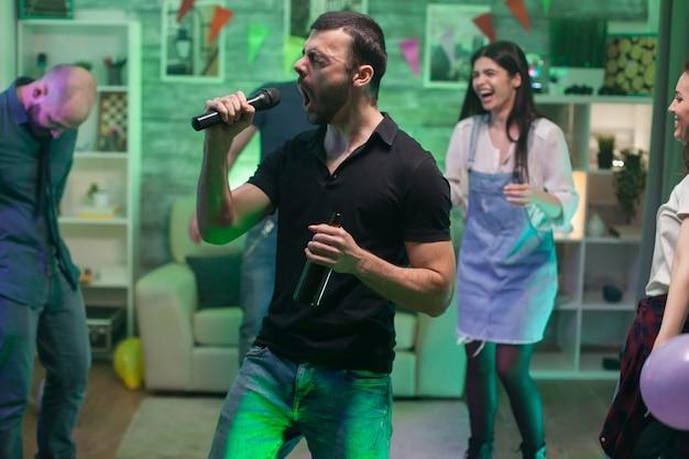 Homme barbu chantant une chanson rock au micro tout en faisant la fête avec ses amis.