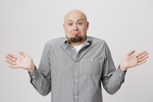 Homme barbu chauve confus écartant les mains sur le côté sans aucune idée