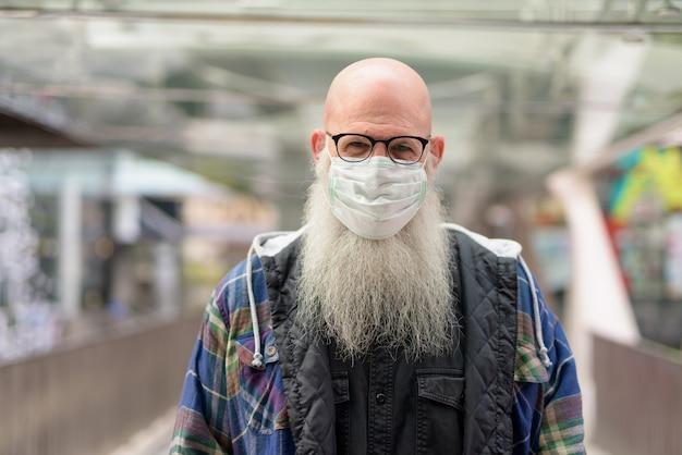 Homme barbu chauve mature avec masque et lunettes pour se protéger contre l'épidémie de virus corona et la pollution