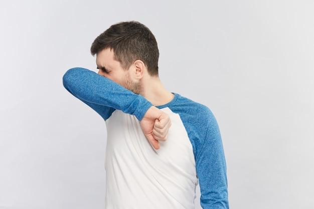 Homme barbu en chemise bleue et blanche éternuant dans son coude pour protéger les autres du coronavirus, espace copie
