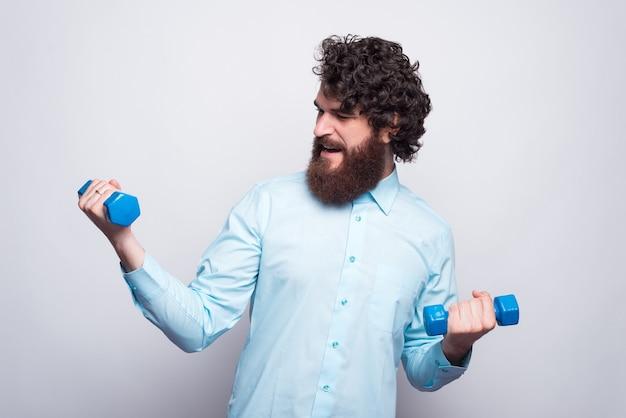 Homme barbu en chemise bleue décontractée travaillant avec de petits haltères.