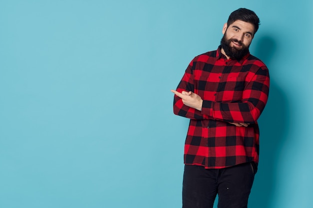 Homme barbu en chemise à carreaux fond bleu studio fashion