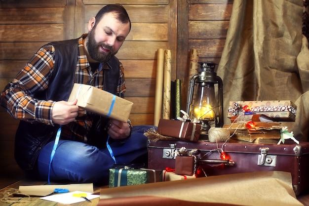 Homme barbu en chemise et gilet emballe des cadeaux de noël se présentant à la caméra dans une décoration en bois