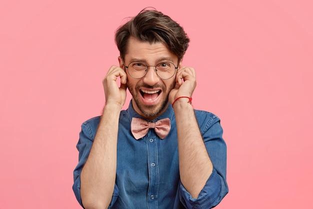 Homme barbu en chemise en jean et noeud papillon rose