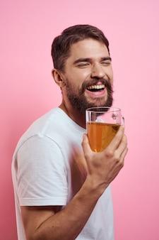 Homme barbu avec une chope de bière sur un fond rose émotions amusantes vue recadrée d'un t-shirt blanc ivre. photo de haute qualité