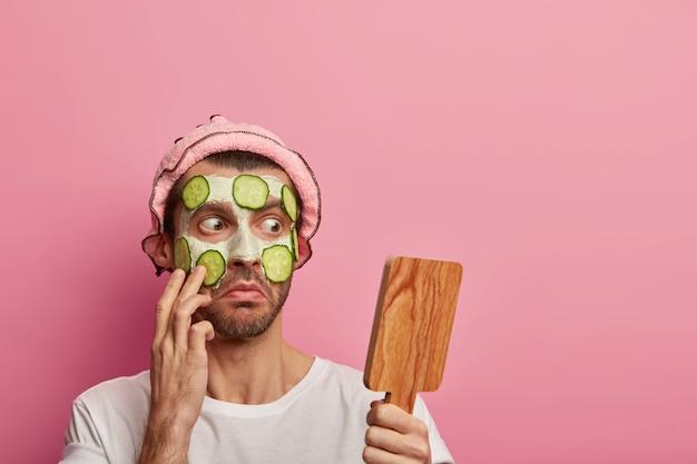 Un homme barbu choqué regarde avec embarras au miroir