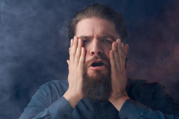 Homme barbu cigarettes vape posant des émotions en gros plan
