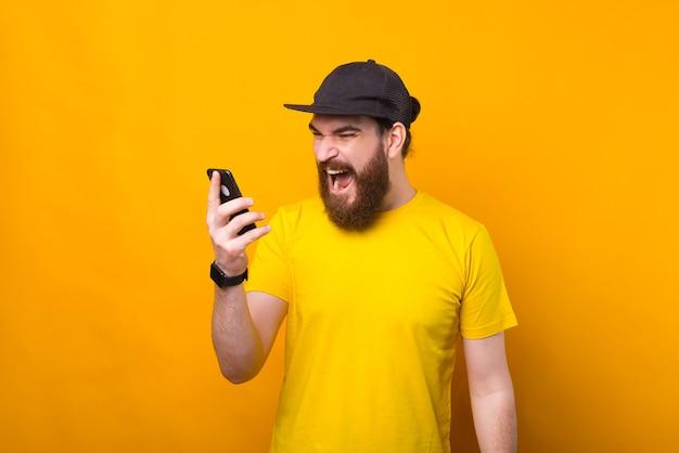 Homme barbu en colère criant au smartphone tout en parlant avec quelqu'un