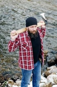 Homme barbu en colère avec une hache traverse la forêt d'hiver