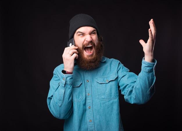 Homme barbu en colère parlant au téléphone sur fond sombre