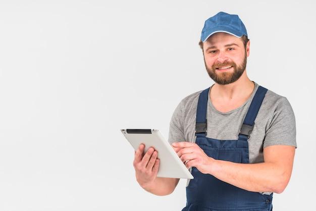 Homme barbu en combinaison avec tablette