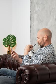 Homme barbu concentré avec des lunettes et un smartphone à la main assis sur une chaise