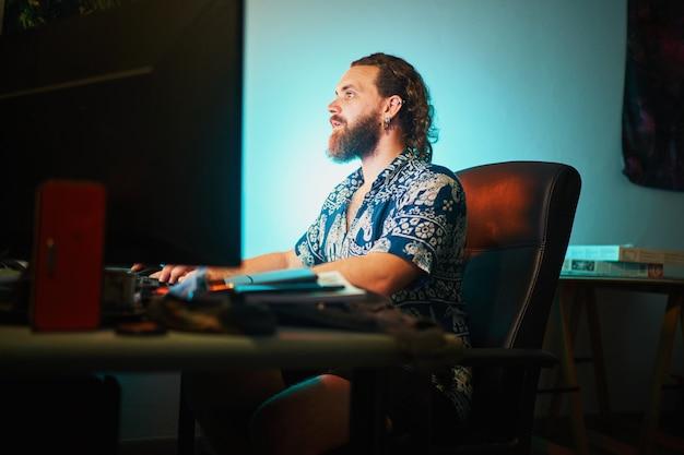 Un homme barbu concentré utilise un ordinateur contre la lumière sarcelle assis sur une chaise