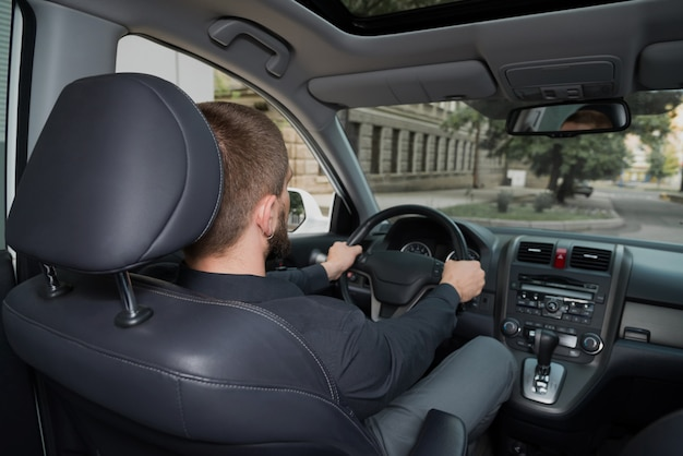 Homme barbu conduisant une auto.