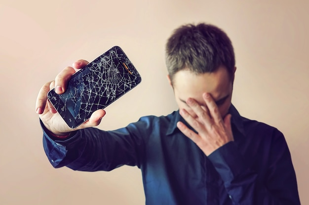 Un homme barbu et contrarié tient une tablette ou un smartphone hors d'usage. sur fond clair. écran cassé