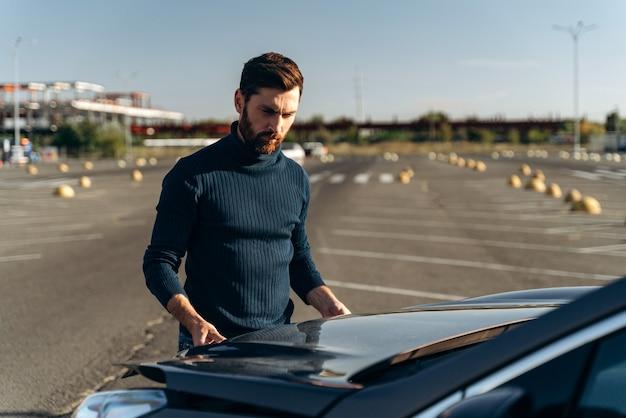 Homme barbu contrarié vérifiant le moteur de sa voiture après une panne sur la route. un homme sérieux se tient devant le capot. notion de transport
