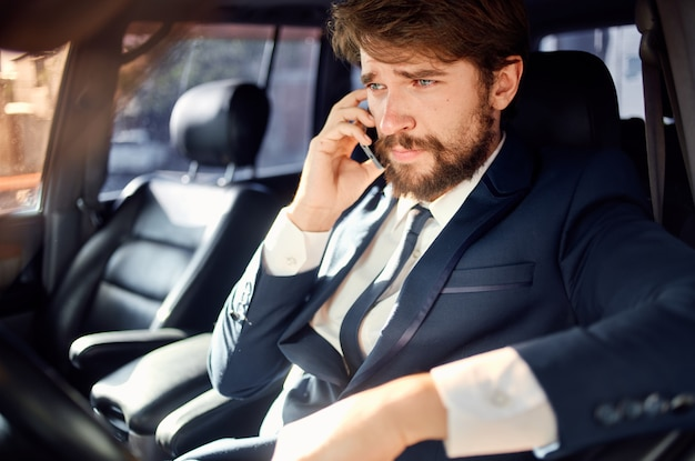 Homme barbu en costume dans une voiture un voyage au travail communication par téléphone
