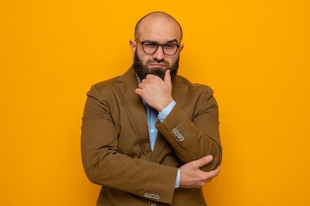 Homme barbu en costume marron portant des lunettes regardant avec une expression pensive avec la main sur son menton