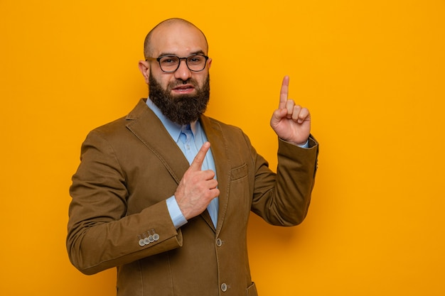 Homme barbu en costume marron portant des lunettes à sourire confiant pointant avec l'index vers le haut