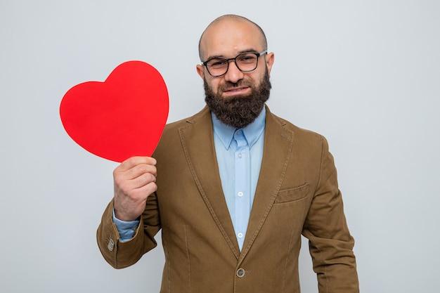 Homme barbu en costume marron portant des lunettes tenant un coeur en carton à sourire gaiement heureux et positif