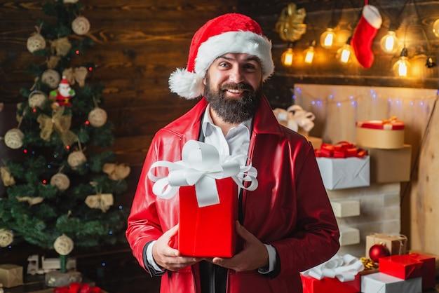 Homme barbu en costume de père noël tenant un cadeau
